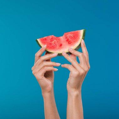 human hands holding watermelon slice