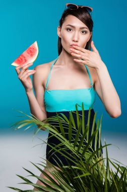 Portrait of young asian woman in swimsuit eating watermelon and looking at camera stock vector