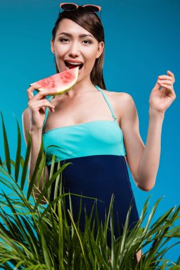asian woman in swimsuit eating watermelon