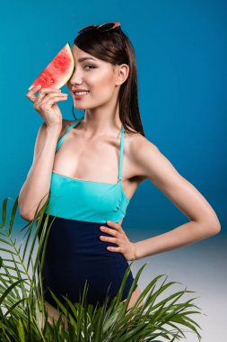 Portrait of asian girl in swimsuit holding watermelon piece stock vector