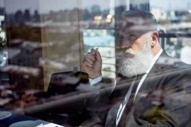 Concentrated mature bearded businessman behind window stock vector