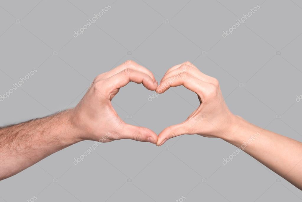 Cropped view of couple making heart sign of hands, isolated on grey stock vector