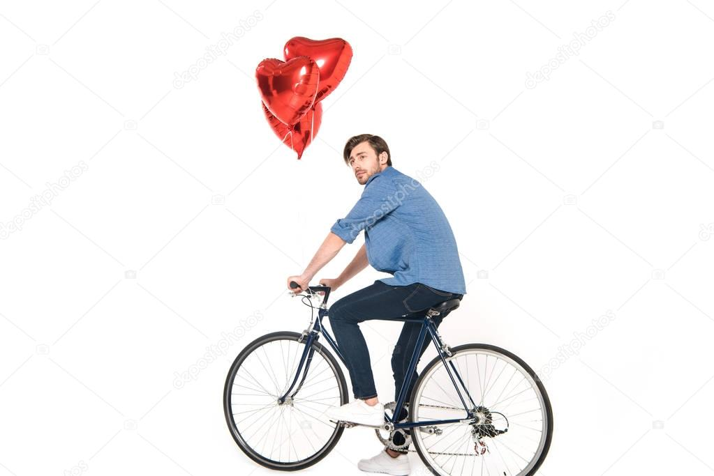 man riding bicycle with balloons