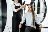hairdresser brushing hair of woman