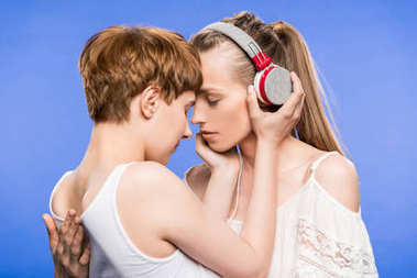Lesbian couple hugging and listening to music