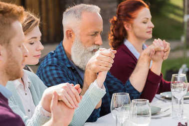 family praying during dinner