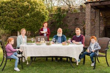 family having dinner at countryside