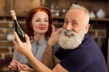 senior couple with bottle of wine