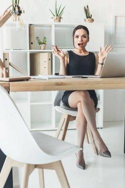 surprised businesswoman at desk