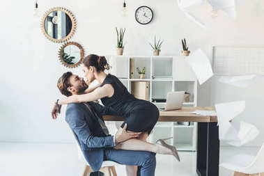 Woman kissing man sitting on chair