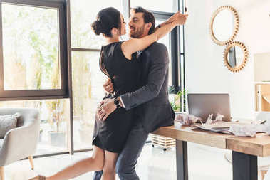 Young couple embracing in office
