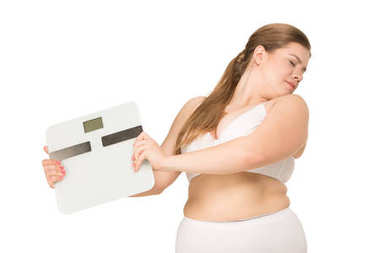 overweight woman holding scales