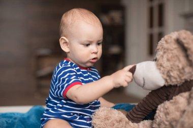 boy playing with teddy bear