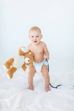 Adorable small baby boy standing on bed and holding stethoscope with teddy bear, 1 year old baby concept stock vector