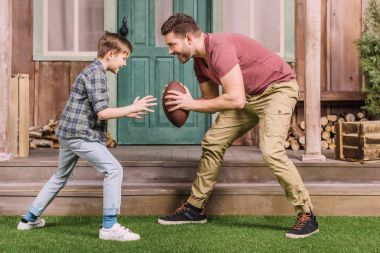 father with son playing with ball at backyard