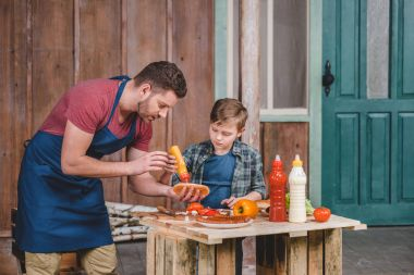 Father and son cooking hot dog