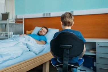 son sitting near sick father at ward