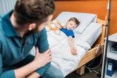 Papa in der Nähe von Sohn im Krankenhausbett