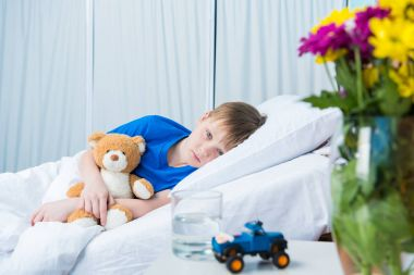 Sick little boy hugging teddy bear and lying in hospital bed stock vector