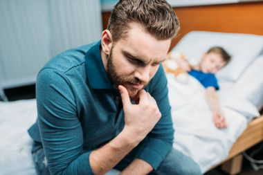 Dad near son in hospital bed