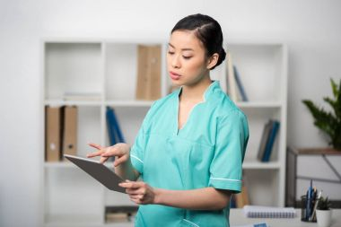 asian internist with digital tablet