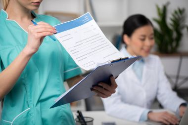 Partial view of doctor looking at clipboard with colleague behind stock vector