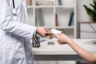 doctor giving card to patient