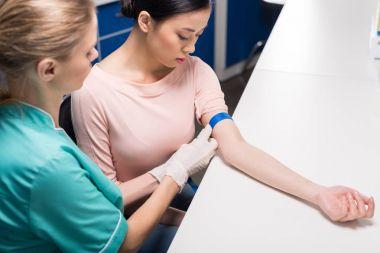 nurse preparing patient to blood analysis