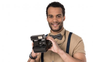 Handsome young african american man holding instant camera and smiling stock vector