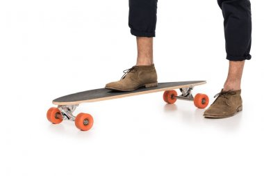 Cropped shot of stylish young man standing on skateboard isolated on white stock vector