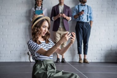 stylish woman taking selfie on smartphone