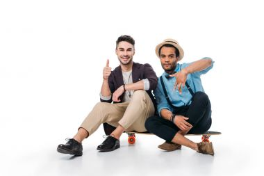 friends sitting on skateboard with hand gestures