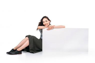 woman sitting and holding blank board