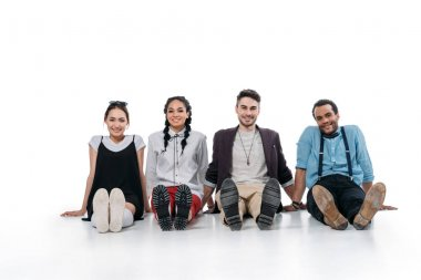 smiling multiethnic friends sitting on floor