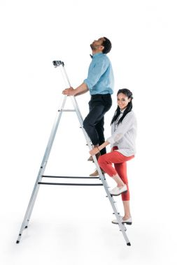 african american couple climbing on stepladder