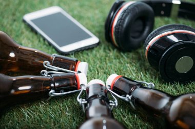 Closeup view of beer bottles with smartphone and headphones lying on grass stock vector