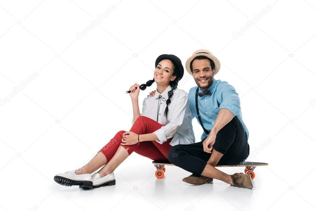 african american couple sitting on skateboard