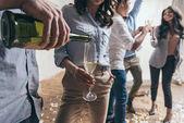 Mladí lidé slaví se šampaňským