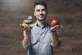 Fotografie Man with hamburger and apple