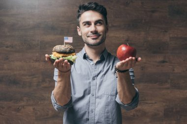 Man with hamburger and apple