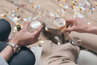 women celebrating and drinking champagne at home