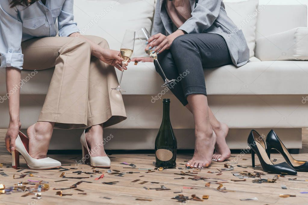 women drinking champagne while resting on sofa