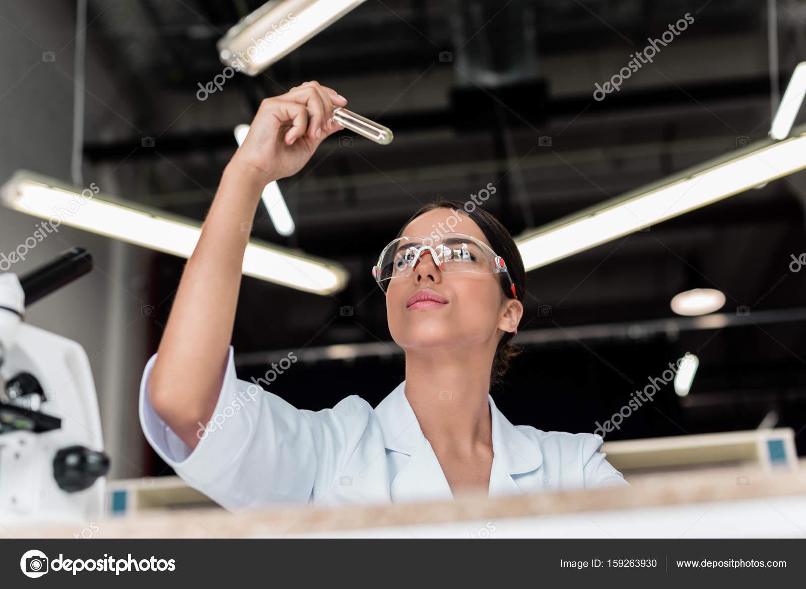 ec7ce8912c Επαγγελματική νεαρό επιστήμονα σε προστατευτικά γυαλιά κρατώντας σωλήνα  δοκιμής στο εργαστήριο — Εικόνα από ...