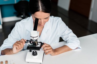 Scientist with microscope in lab