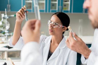 Young scientists in white coats examining test tubes with reagents in chemical lab stock vector