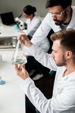 Scientists examining flask