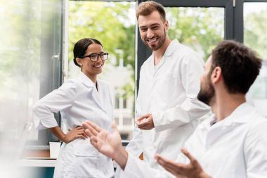 Team of professional scientists in white coats smiling and talking in laboratory stock vector