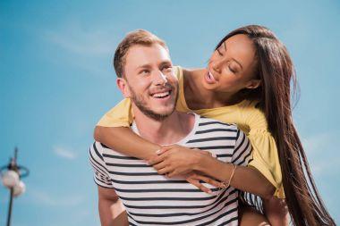 Multiethnic couple piggybacking in city