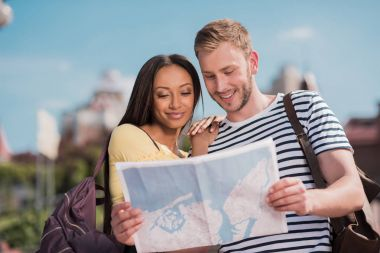 Young smiling multiethnic couple of tourists looking at map in city stock vector