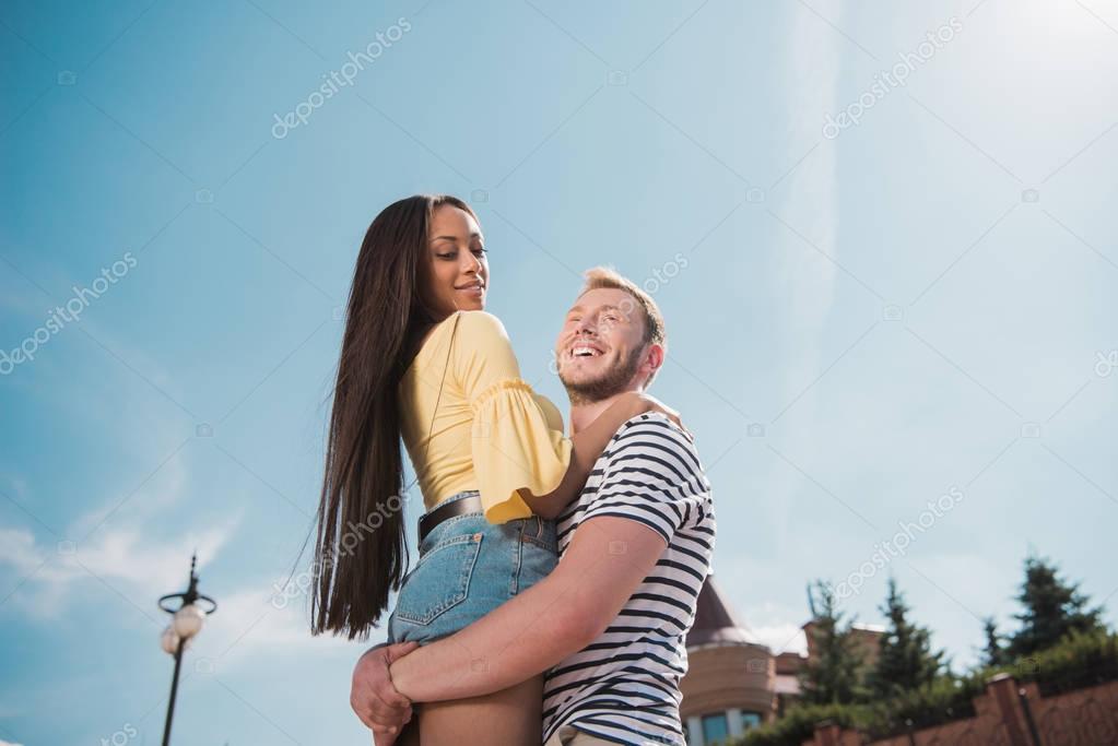 Multiethnic couple hugging in city